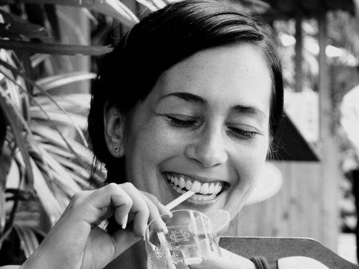 Close-up of cheerful woman having drink while sitting outdoors