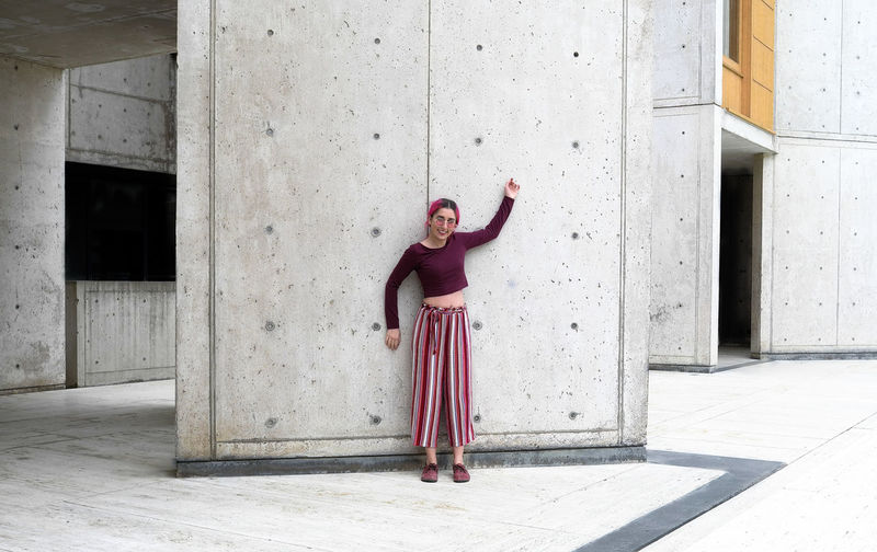 Full Length Of Woman Standing Against Concrete Wall