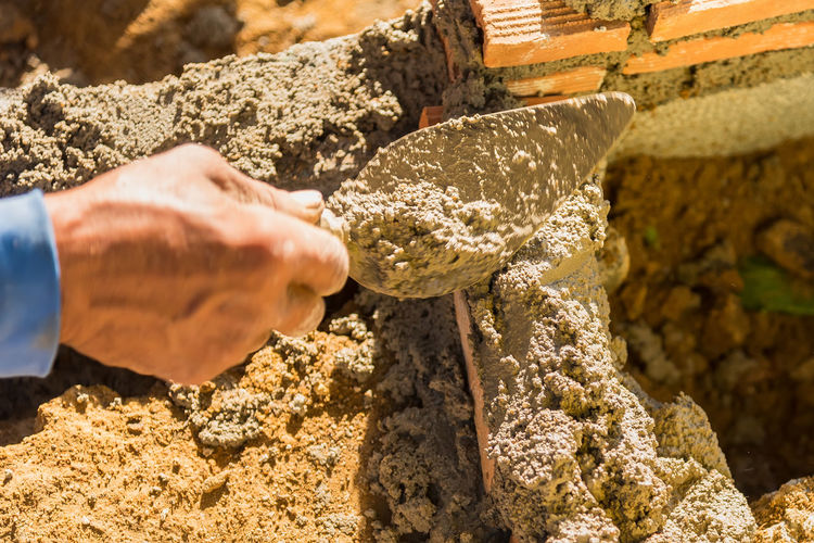 Close-up of worker hand holding with spatula at construction site
