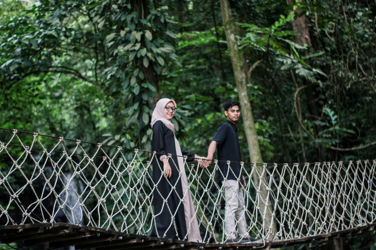 Portrait of couple standing on footbridge in forest