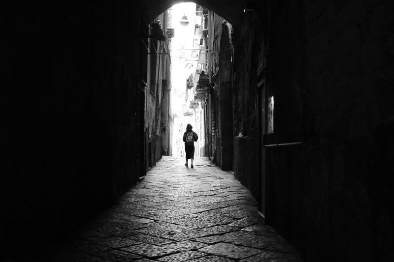Rear View Of Person Walking In Alley