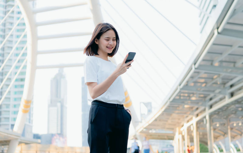 Woman stand and holding a smartphone, using cell phone on lifestyle. Technology for communication concept. Wireless Technology Technology Mobile Phone Communication Connection Standing One Person Young Adult Three Quarter Length Using Phone Holding Smart Phone Women Portable Information Device Adult Young Women Telephone Focus On Foreground Lifestyles Hairstyle