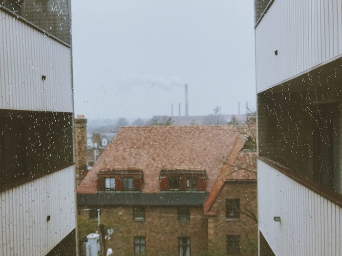 Buildings seen through wet window during rainy season