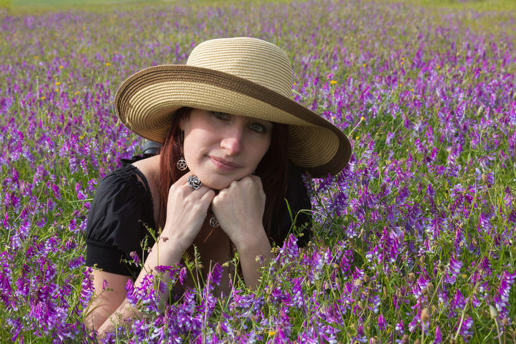 Portrait of young woman lying amidst pink flowers on field