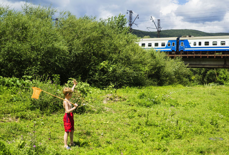 Boy Standing In Grass By Railroad Track