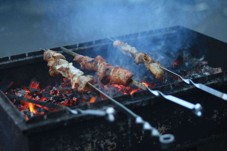 Meat on barbecue grill against sky at night