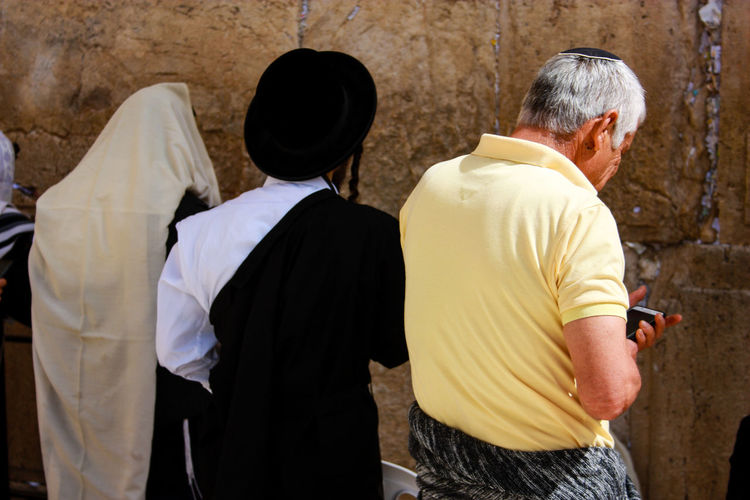 Rear view of men standing against wailing wall