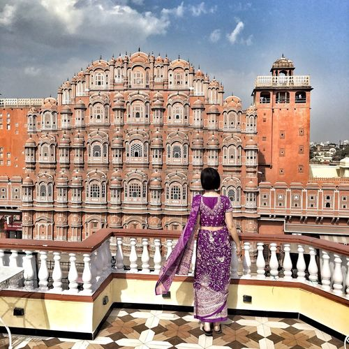 Rear view of woman standing against historical building