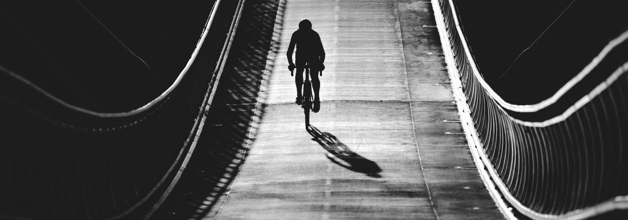 Silhouette man cycling on bridge