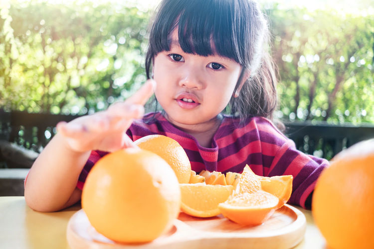 Fruit and Vegetable for Kids Concept. Little Cute 3-4 Years Old Girl with Sliced Orange on Wooden Plate. Fresh Juicy Fruit in Summer Orange Summer Kids Asian  Happy Slices Cute Playful Concept Child Girl Smile Face Smiling Day Children Fun Lifestyle Portrait Joy Young Happiness Cheerful Playing Childhood Model 3 Years Plate Fruit Vitamin Food Sliced Healthy Organic Sweet Juicy Citrus  Natural Table Freshness Tropical Delicious Cut Juice Wooden House Home Outdoor Copy Space