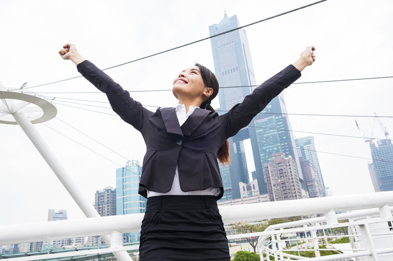 Confident Young Businesswoman Standing With Clenched Fist On Bridge