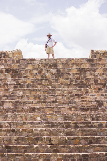 Full Length Of Mature Man Standing On Wall Against Cloudy Sky