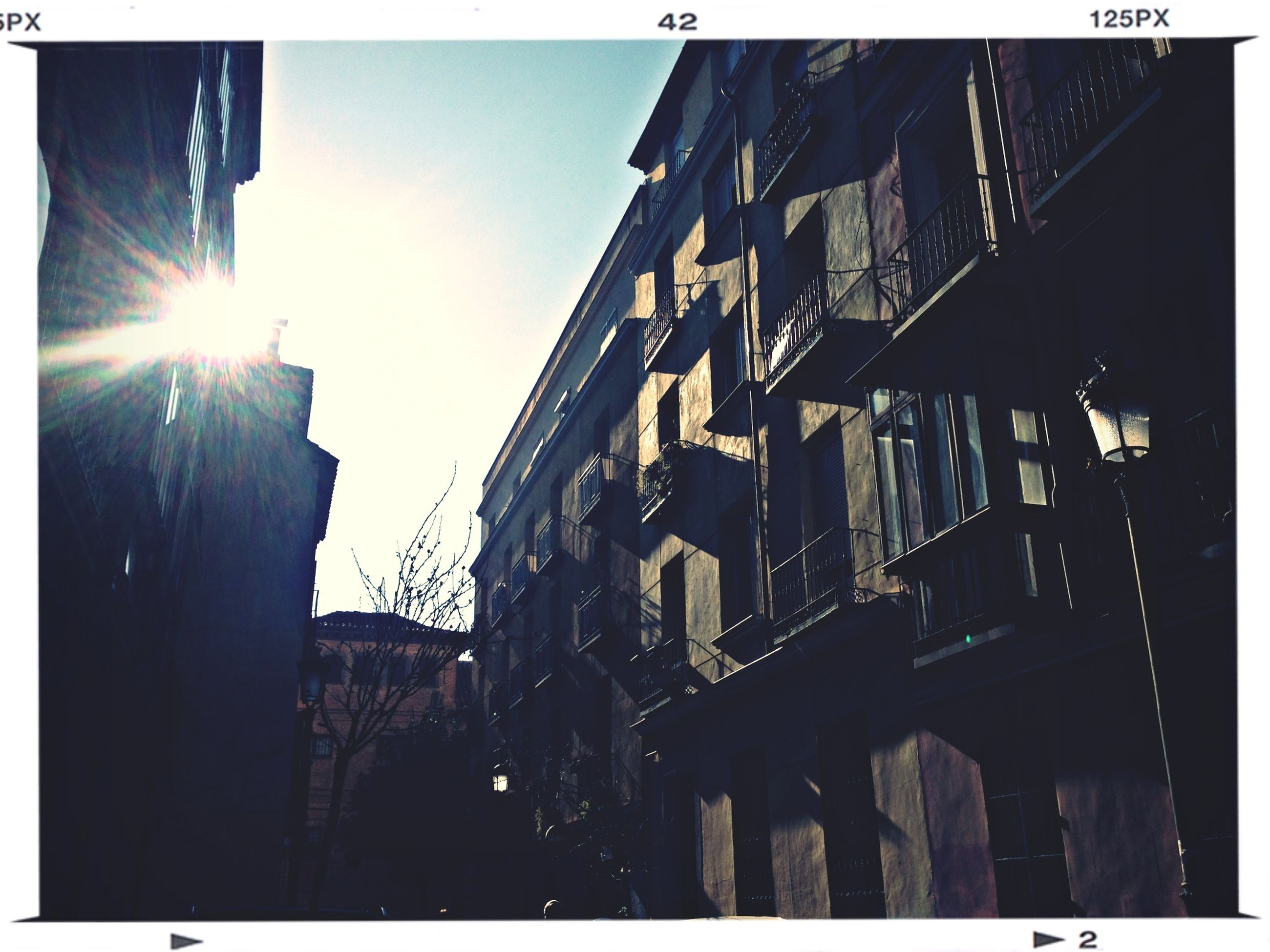 building exterior, architecture, built structure, transfer print, low angle view, sunlight, city, sunbeam, sun, building, auto post production filter, sky, lens flare, residential building, residential structure, city life, outdoors, day, window, sunny