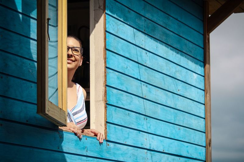 Smiling young woman looking through house window