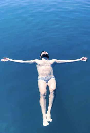 Full length of man floating on water in sea