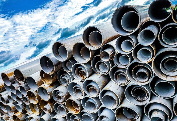 High angle view of stack of pipes on sea against sky