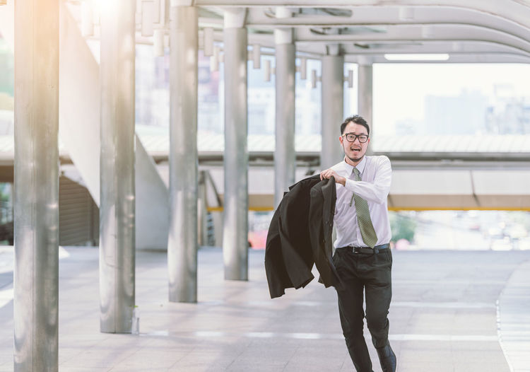 Businessman wearing blazer while walking on footbridge in city