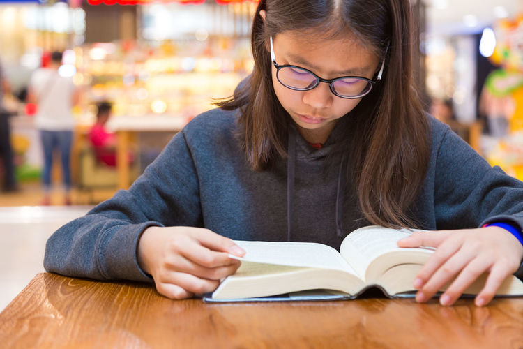 Asian female teenager spending her free time reading her book Books Fiction Reading, PA. Woman Book Childhood Education Eyeglasses  Front View Girl Headshot Hobby Indoors  Learning Leisure Activity Lifestyles One Person Real People Sitting Spare Time Studying Table Teenager Young Adult