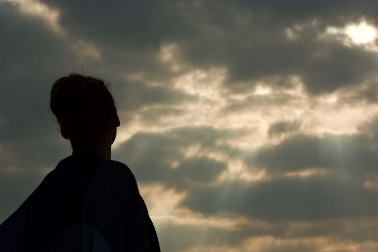 Low angle view of silhouette woman against cloudy sky during sunset