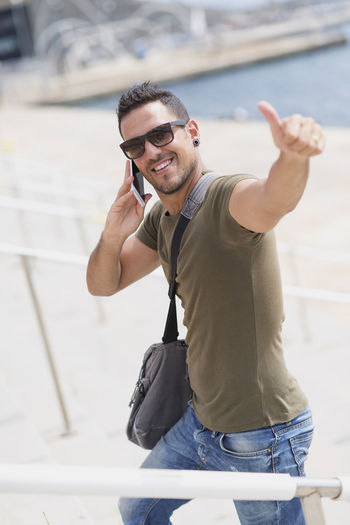 Portrait of man talking on mobile phone in city