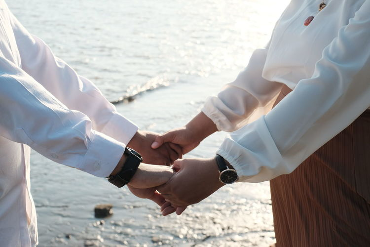 Midsection of couple holding hands at beach