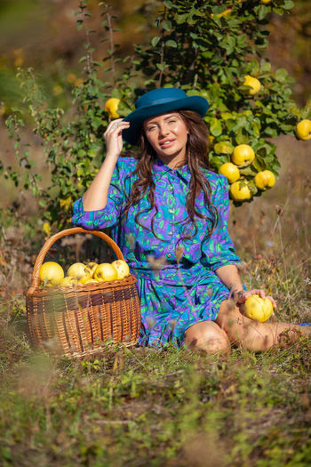 Portrait of woman with fruits sitting on land
