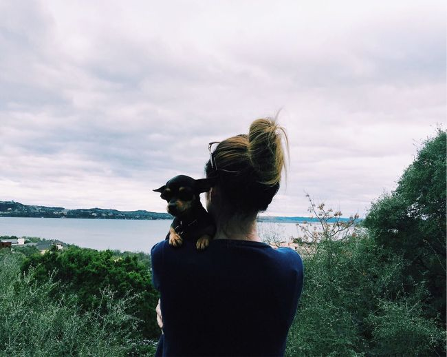 Rear view of woman holding dog against lake