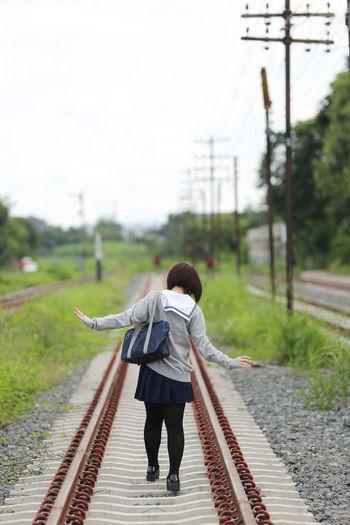 Rear View Of Woman In School Uniform On Railway Tracks