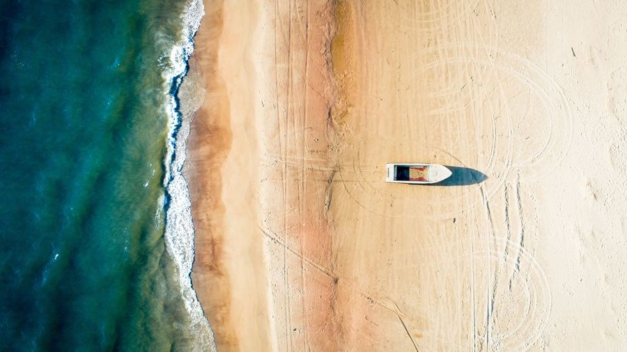 Boat on the Beach Sea Ocean Aerial Drone  Vertical Blue Minimal Travel Tourism Sand Dune Exotic Hot Top Down View Sailing Boating Adventure Nature Island EyeEm Selects Water Wave Beach Sea Sand Sky Boat Water Sport Rafting