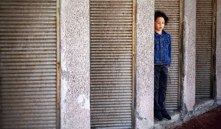 Thoughtful boy standing by building window