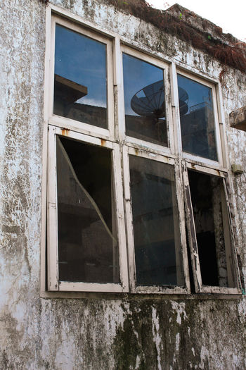 Low angle view of broken glass window of old building