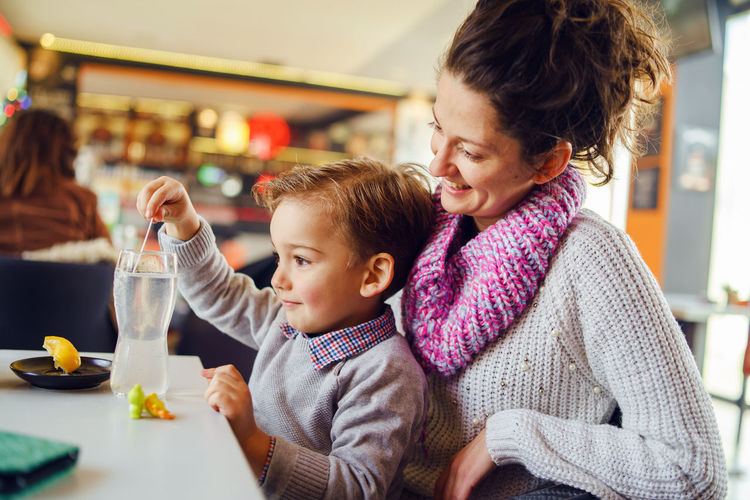 Smiling woman sitting with son at table in restaurant