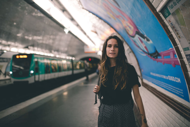 Portrait of woman standing at railroad station