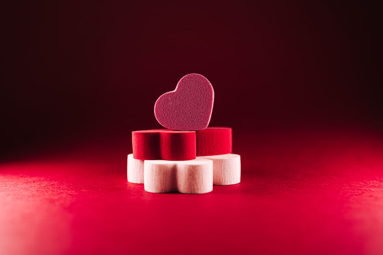 Close-up of heart shape on pink table against colored background