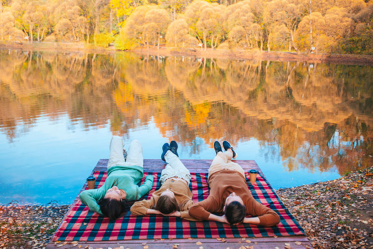 People relaxing in lake during autumn