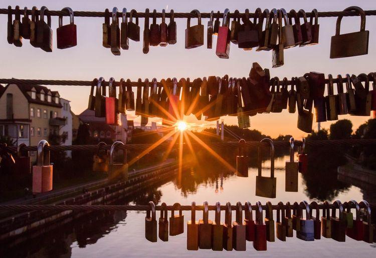 Locks Hanging On Railing Over River Against Sky During Sunset