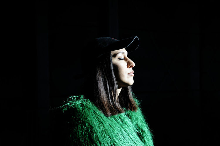 Portrait of young woman wearing hat against black background