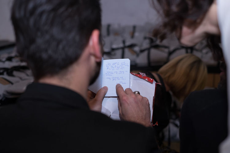 Rear view of man pointing on notepad
