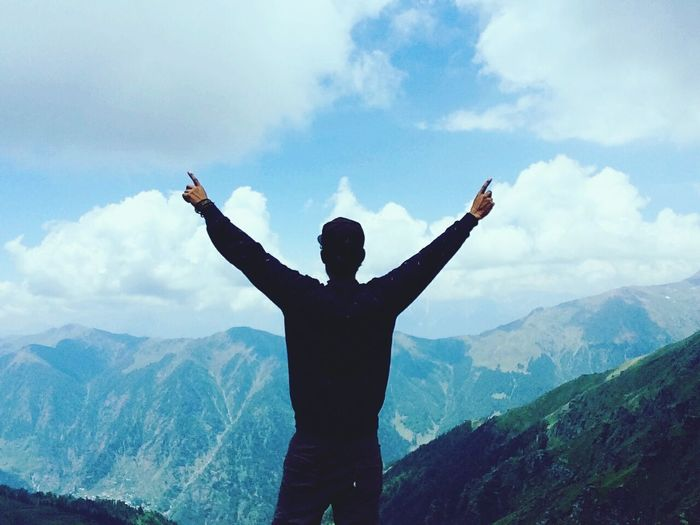 Rear view of man standing with arms outstretched against himalaya mountain
