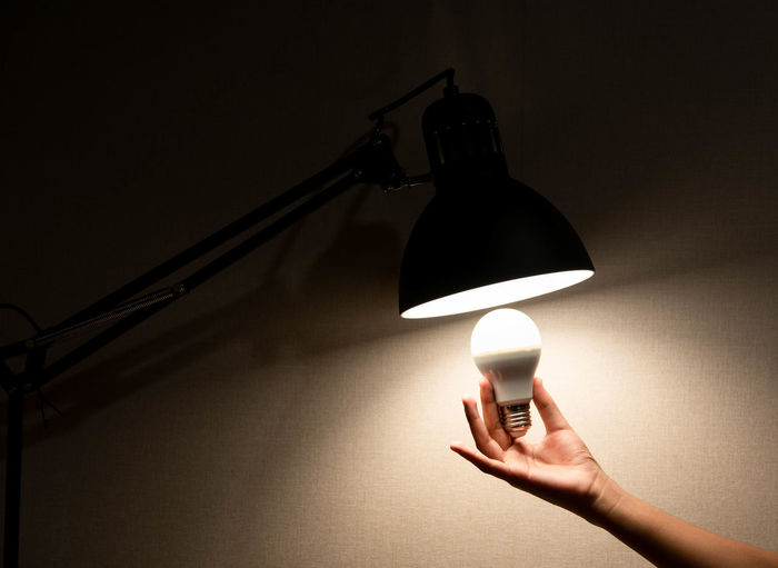 Close-up of hand holding light bulb