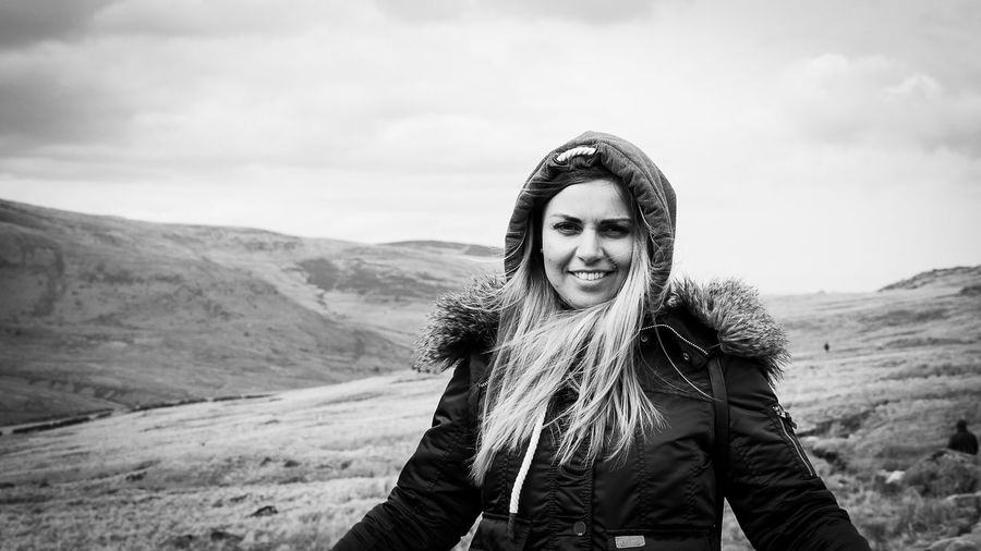 Beauty In Nature Clothing Emotion Front View Happiness Hood - Clothing Leisure Activity Lifestyles Looking At Camera Mountain Nature One Person Portrait Real People Sky Smiling Standing Warm Clothing Young Adult Young Women