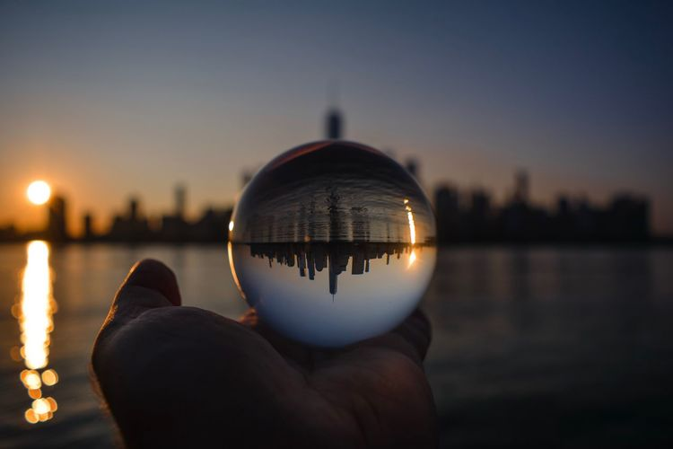 Person holding crystal ball against sky during sunset
