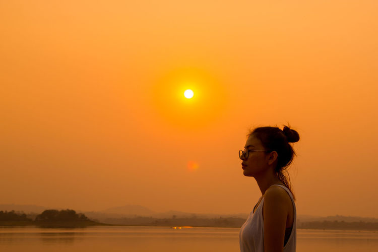 Woman standing against lake during sunset