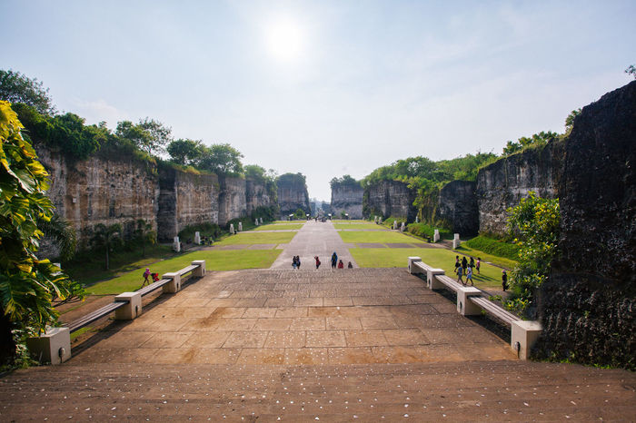 Architecture Building Exterior City Life Clear Sky Day Diminishing Perspective Footpath Garden Garuda Wisnu Kencana Large Group Of People Outdoors Park Park - Man Made Space Pathway Person Sky Sunlight Sunny The Way Forward Tourism Tourist Travel Destinations Tree Vacations Walkway