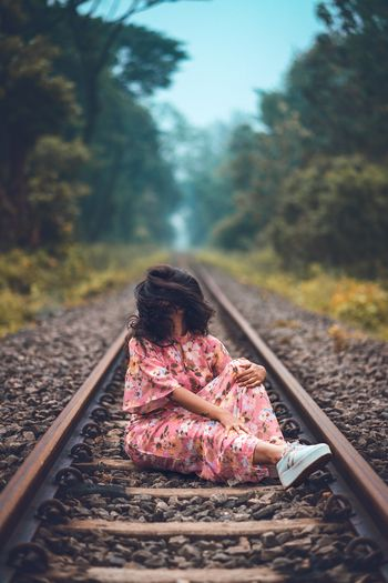 Teenage girl sitting on railroad track