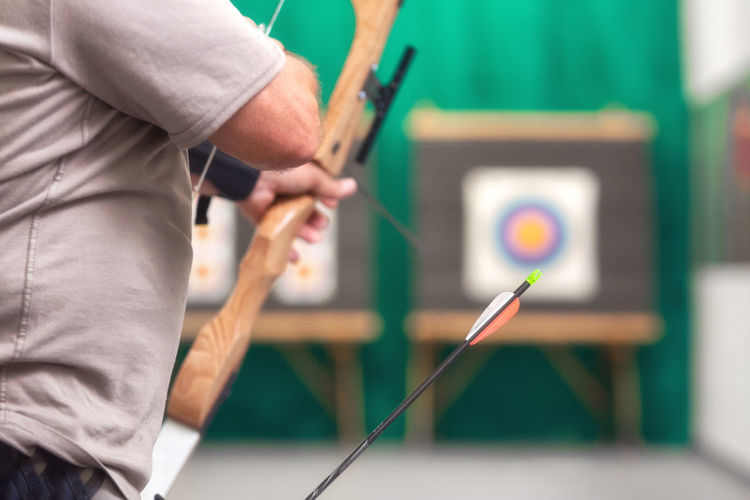 Midsection of man playing archery