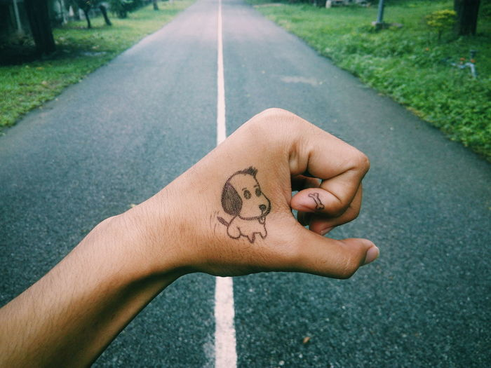 Cropped Image Of Hand With Dog Sketch Against Empty Road
