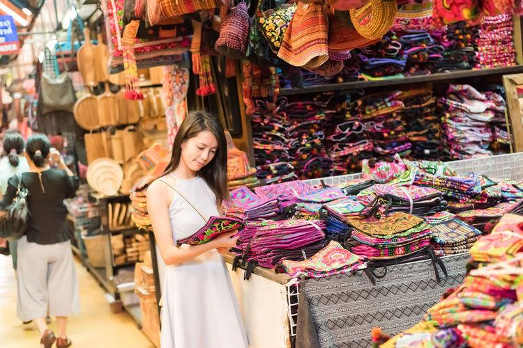 Woman buying bag at market stall