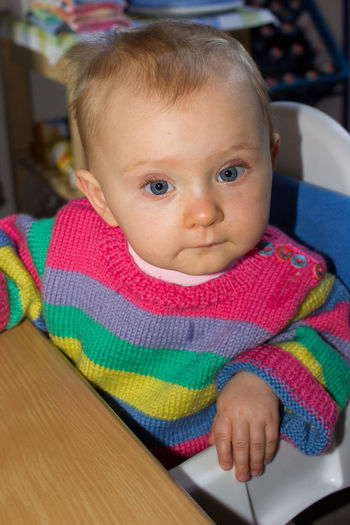 little child with blue eyes in colorful sweater sitting at kitchen table Kitchen Home At Home Home Interior European  Caucasian Caucasian Ethnicity Blue Eyes Blue Toddler  Toddlerlife Baby Babyhood Cute Sweet Adorable Child Childhood Sitting Looking At Camera Front View Real People Indoors  Blond Hair Blonde Blond Human Face Portrait Innocence Indoors  Colorful Pullover Knitted Sweater Vertical High Angle View Young One Person Toddler  Clothing Focus On Foreground