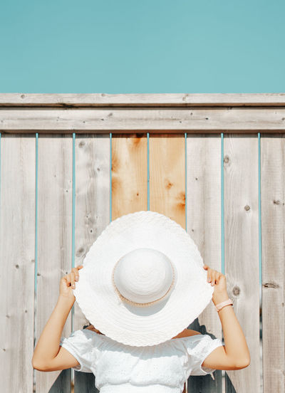 Young woman covering face with hat against wooden wall outdoors